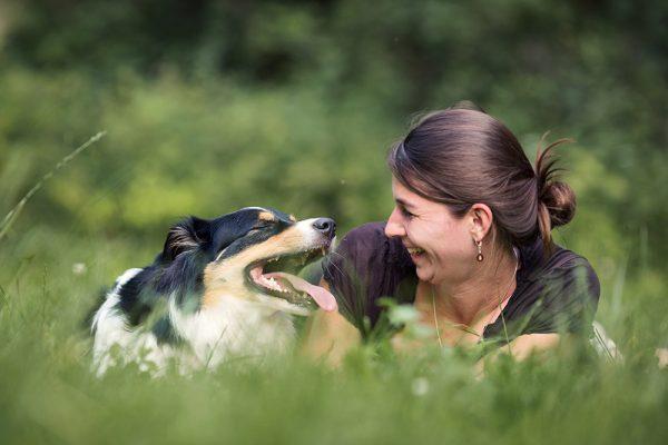 Tierkommunikatorin liegt in Wiese mit Australian Shepherd Hund