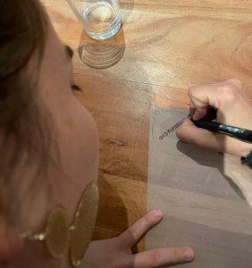 Frau Susanne Eggers schreibt auf Schrumpffolie ihre Telefonnummer