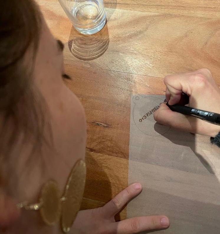 Frau schreibt Telefonnummer in einen Kreis auf Schrumpffolie