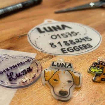 selbstgemachte Hundemarke und Schlüsselanhänger in Motiven Giraffe und Hundekopf liegen auf braunem Tisch
